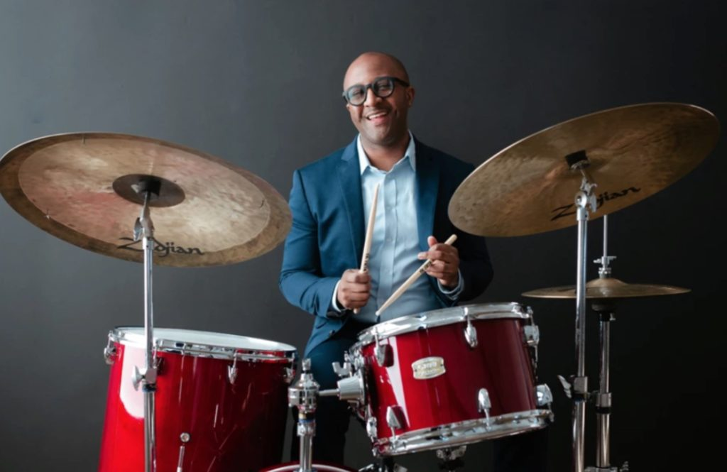 Quincy Davis sitting at a red Yamaha drum set with Zildjian cymbals